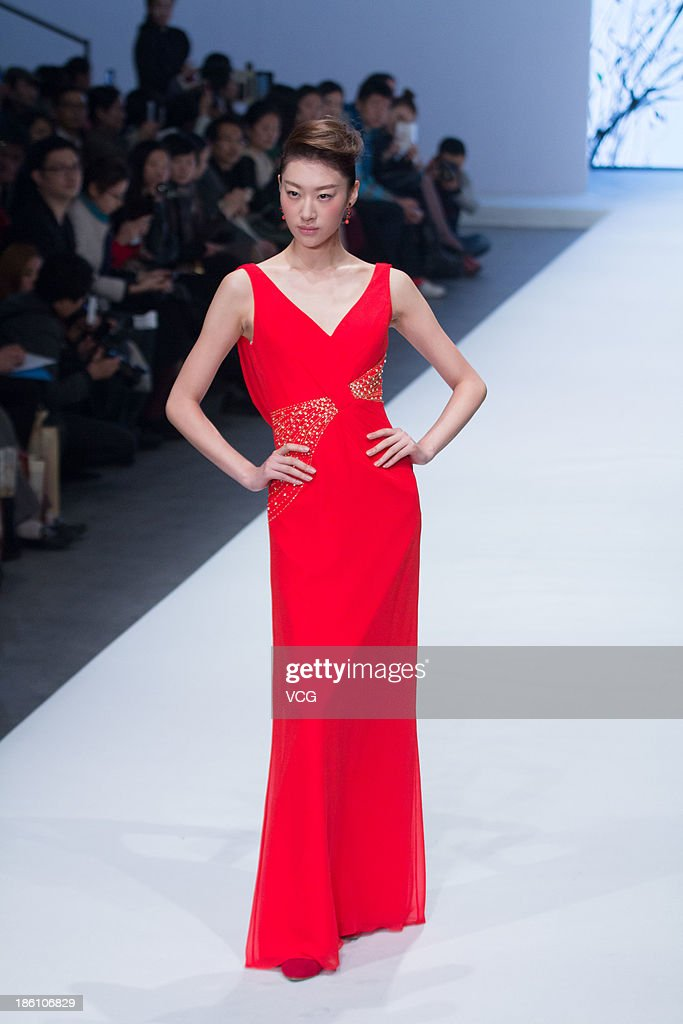 A model showcases designs by Cai Zhonghan on the runway at the Famory Cai Zhongha Bridalwear Collection show during Mercedes-Benz China Fashion Week Spring/Summer 2014 at 751 D.Park Central Hall on October 27, 2013 in Beijing, China.