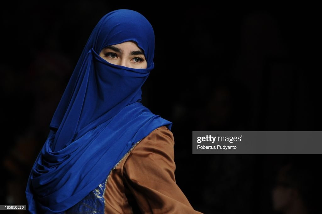 A model showcases designs by Fitria Aulia on the runway at the Glorious Moors show during Jakarta Fashion Week 2014 at Senayan City on October 25, 2013 in Jakarta, Indonesia.