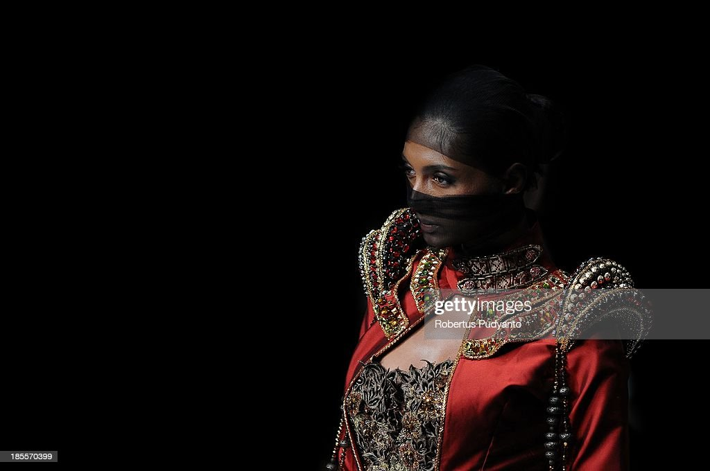 A model showcases designs by Fomalhaut Zamel on the runway at the Byzansation show during Jakarta Fashion Week 2014 at Senayan City on October 22, 2013 in Jakarta, Indonesia.