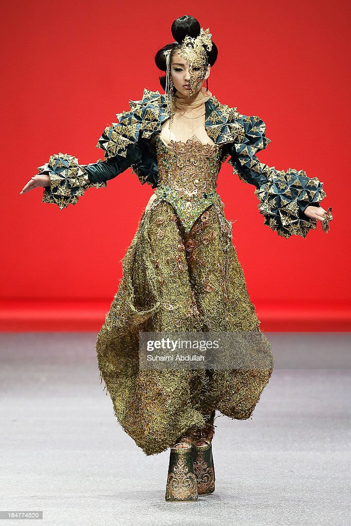 A model showcases designs by Guo Pei on the catwalk on day 8 of Fashion Week 2013 at the Sands Expo & Convention Centre on October 16, 2013 in Singapore.