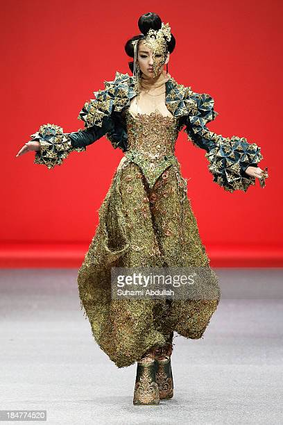 A model showcases designs by Guo Pei on the catwalk on day 8 of Fashion Week 2013 at the Sands Expo Convention Centre on October 16 2013 in Singapore