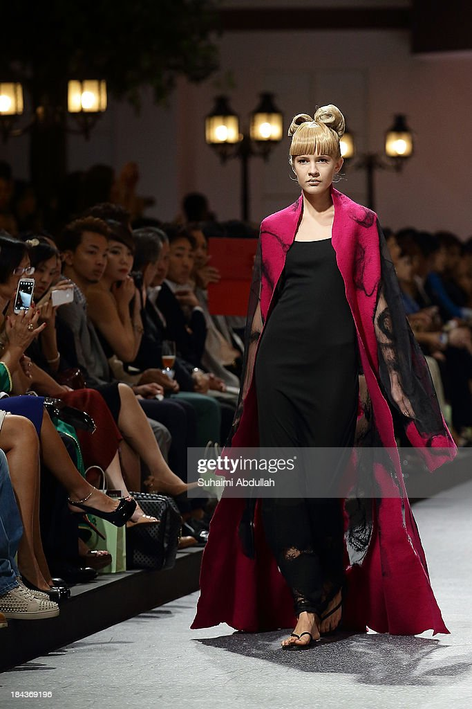 A model showcases designs by Junko Koshino on the catwalk on day 5 of Fashion Week 2013 at the Sands Expo & Convention Centre on October 13, 2013 in Singapore.