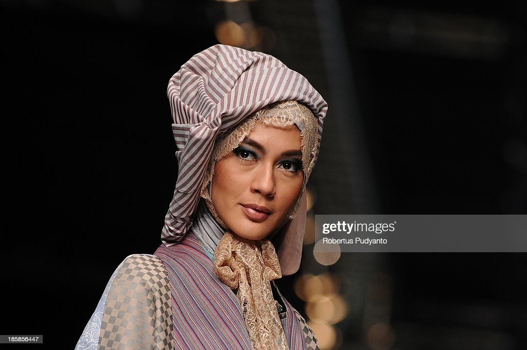 A model showcases designs by Kursien Karzai on the runway at the Dieng Nation show during Jakarta Fashion Week 2014 at Senayan City on October 25, 2013 in Jakarta, Indonesia.