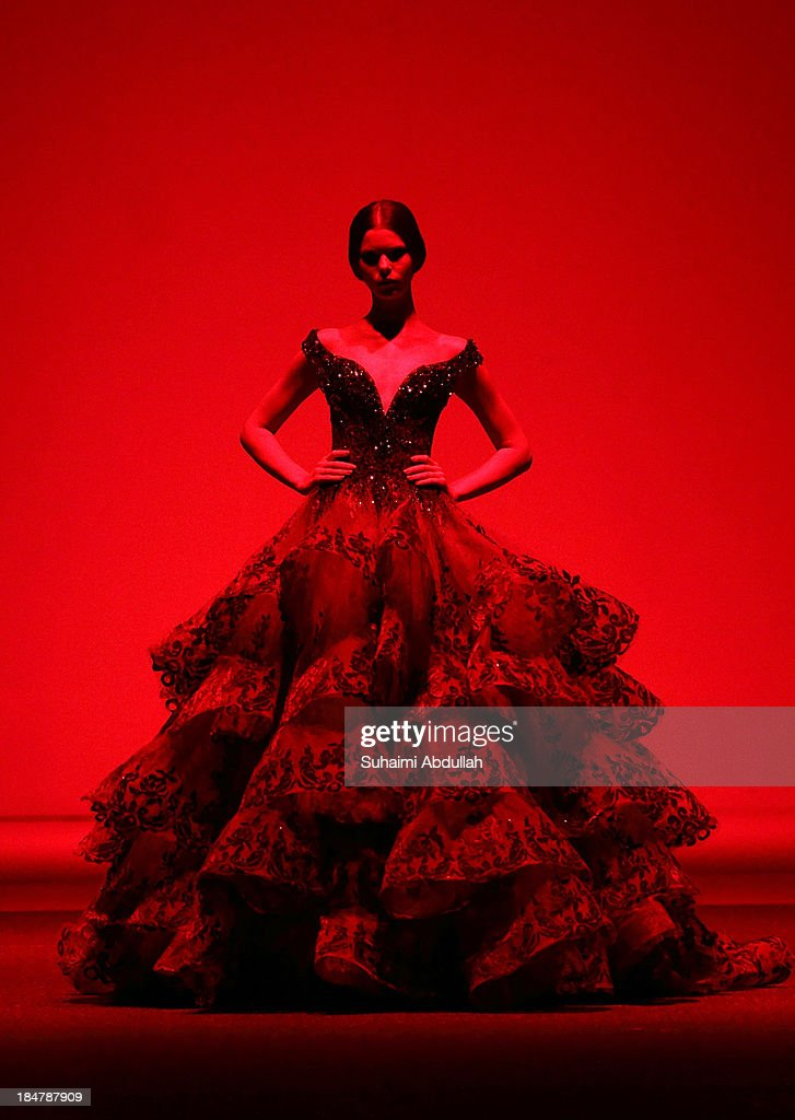 A model showcases designs by Michael Cinco on the catwalk on day 8 of Fashion Week 2013 at the Sands Expo & Convention Centre on October 16, 2013 in Singapore.