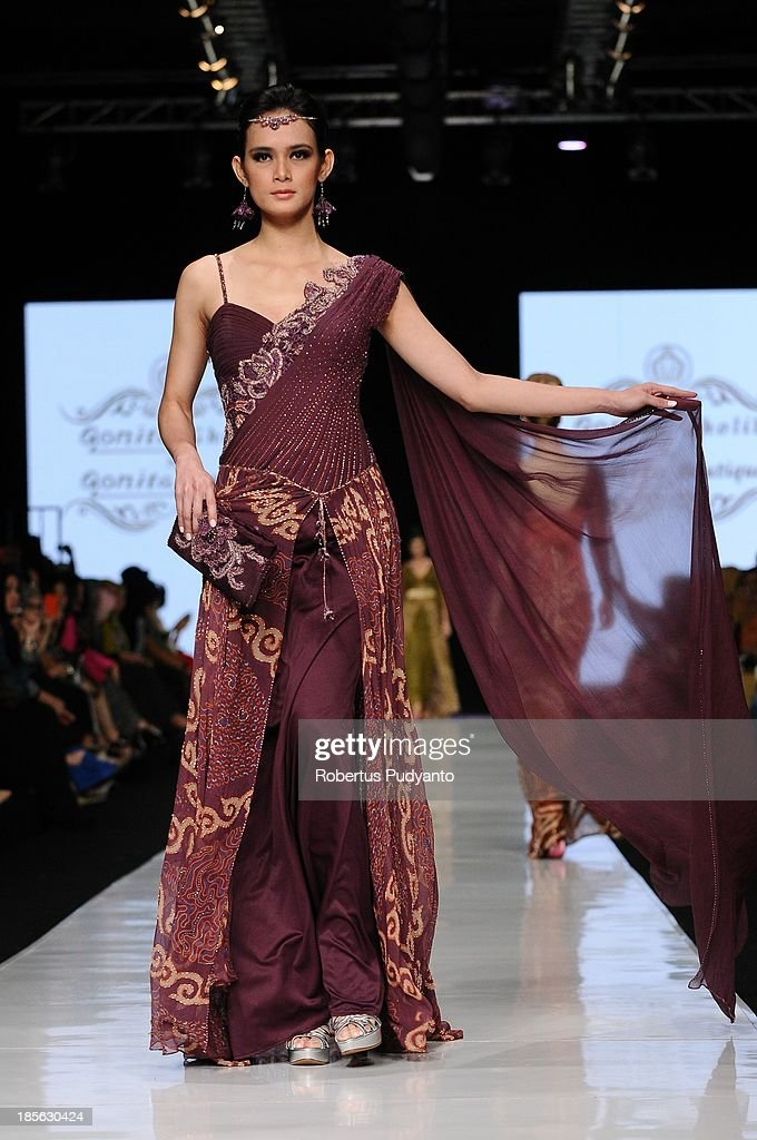 A model showcases designs by Qonita Gholib on the runway at the Romantica Batik show during Jakarta Fashion Week 2014 at Senayan City on October 23, 2013 in Jakarta, Indonesia.