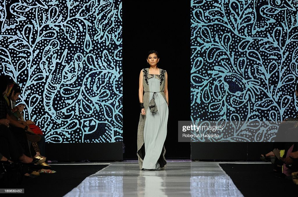 A model showcases designs by Tieka Huza on the runway at the Black Touch show during Jakarta Fashion Week 2014 at Senayan City on October 23, 2013 in Jakarta, Indonesia.
