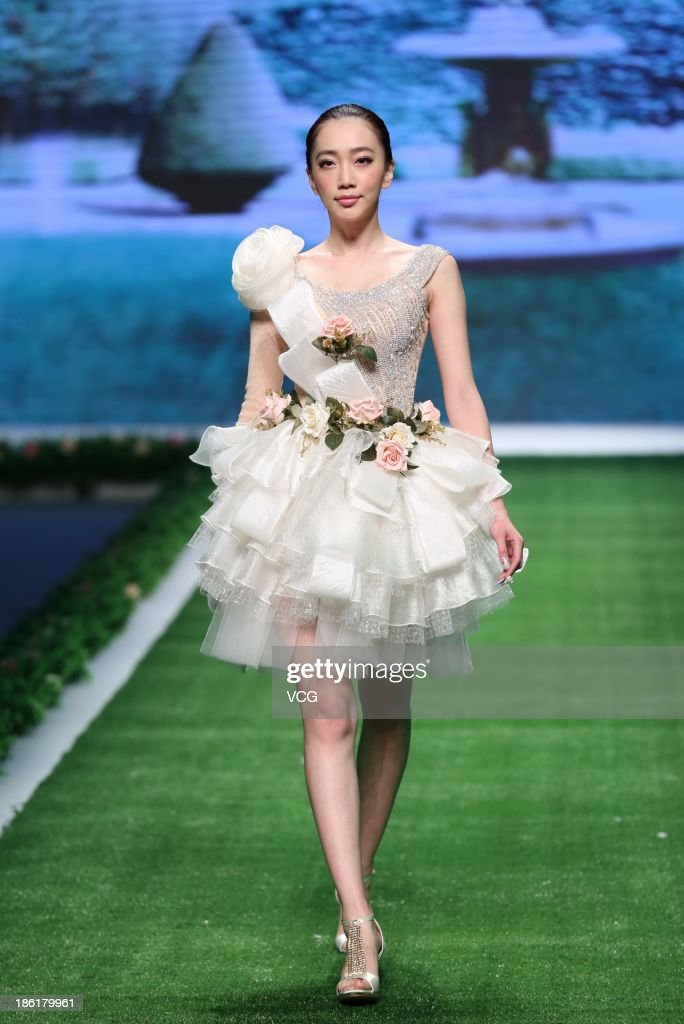 A model showcases designs by Tsai Meiyue on the runway at the TSAIMEIYUE Tsai Meiyue Wedding Dress Collection show during Mercedes-Benz China Fashion Week Spring/Summer 2014 at Beijing Hotel on October 27, 2013 in Beijing, China.