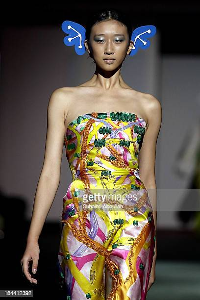 A model showcases designs by Yoshiki Hishinuma on the catwalk on day 5 of Fashion Week 2013 at the Sands Expo Convention Centre on October 13 2013 in...