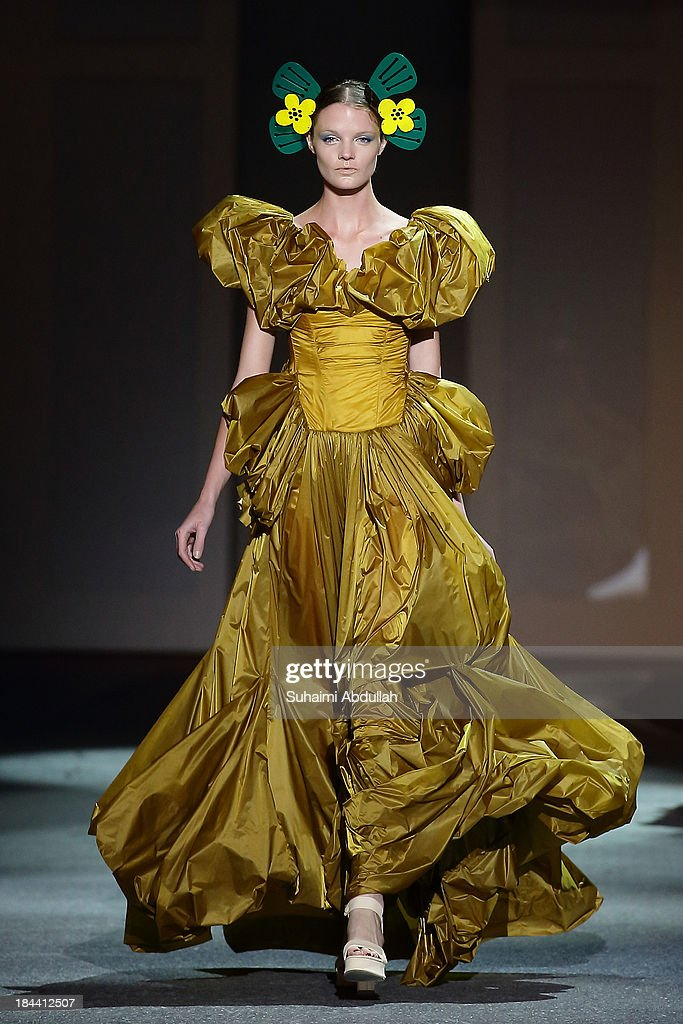 A model showcases designs by Yoshiki Hishinuma on the catwalk on day 5 of Fashion Week 2013 at the Sands Expo & Convention Centre on October 13, 2013 in Singapore.