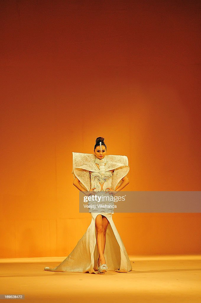 A model showcases designs from the Grand Allure collection by various designers on the runway at the last day of the Philippine Fashion Week Holiday 2013 on May 26, 2013 in Manila, Philippines.