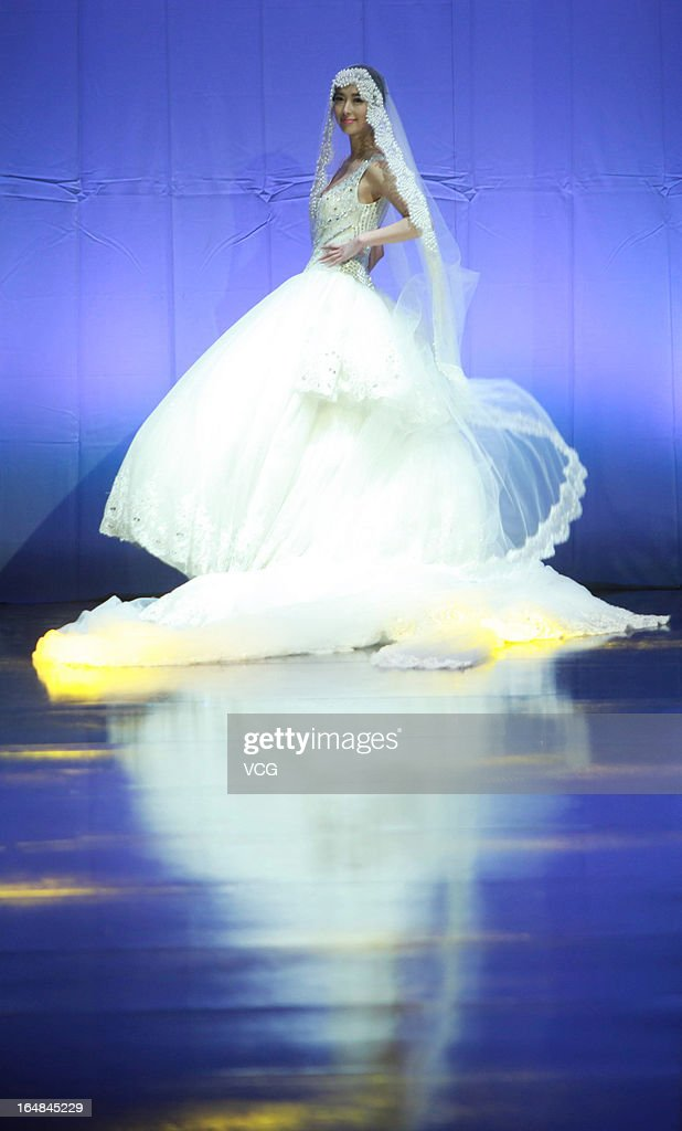 A model showcases designs on the catwalk during the MARK ALPHA OERMA Mark Cheung Wedding Dress collection show on the fifth day of Mercedes-Benz China Fashion Week Autumn/Winter 2013/2014 at 751 D.PARK Workshop on March 28, 2013 in Beijing, China.