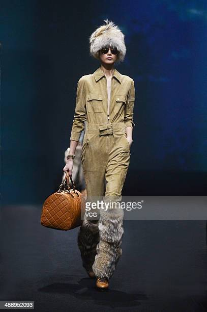 A model showcases designs on the catwalk during the Michael Kors 'Jet Set Experience' event on May 9 2014 in Shanghai China