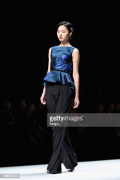 A model showcases designs on the runway at CHUHETINGXIANG Chu Yan Collection show during MercedesBenz China Fashion Week Spring/Summer 2014 at...