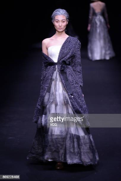 A model showcases designs on the runway at Mid Time Mija Design collection by designer Lv Qing during the MercedesBenz China Fashion Week...