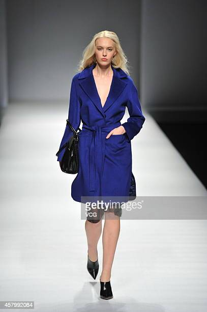 A model showcases designs on the runway at OPEN RUSSIAN FASHION show during the fourth day of the MercedesBenz China Fashion Week Spring/Summer 2015...