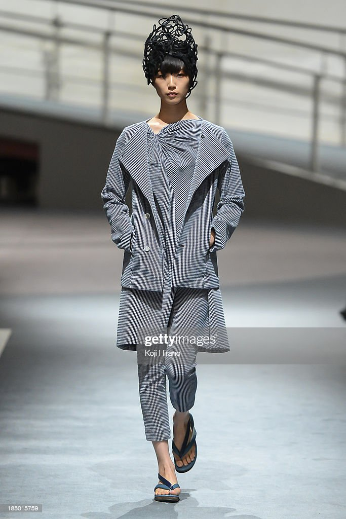 A model showcases designs on the runway during the matohu runway as part of Mercedes Benz Fashion Week TOKYO 2014 S/S at Spiral Garden on October 16, 2013 in Tokyo, Japan.