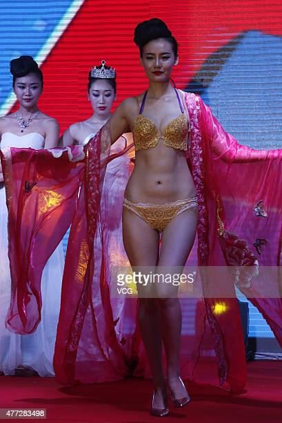 A model showcases gold underwear during the 120th anniversary of Cuihua Gold Shop on June 15 2015 in Zhengzhou China Five designers and four...