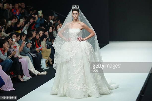 A model showcases wedding dress on the runway at AOLISHA Wei Xinkun Bridal Collection during the MercedesBenz China Fashion Week Spring/Summer 2016...