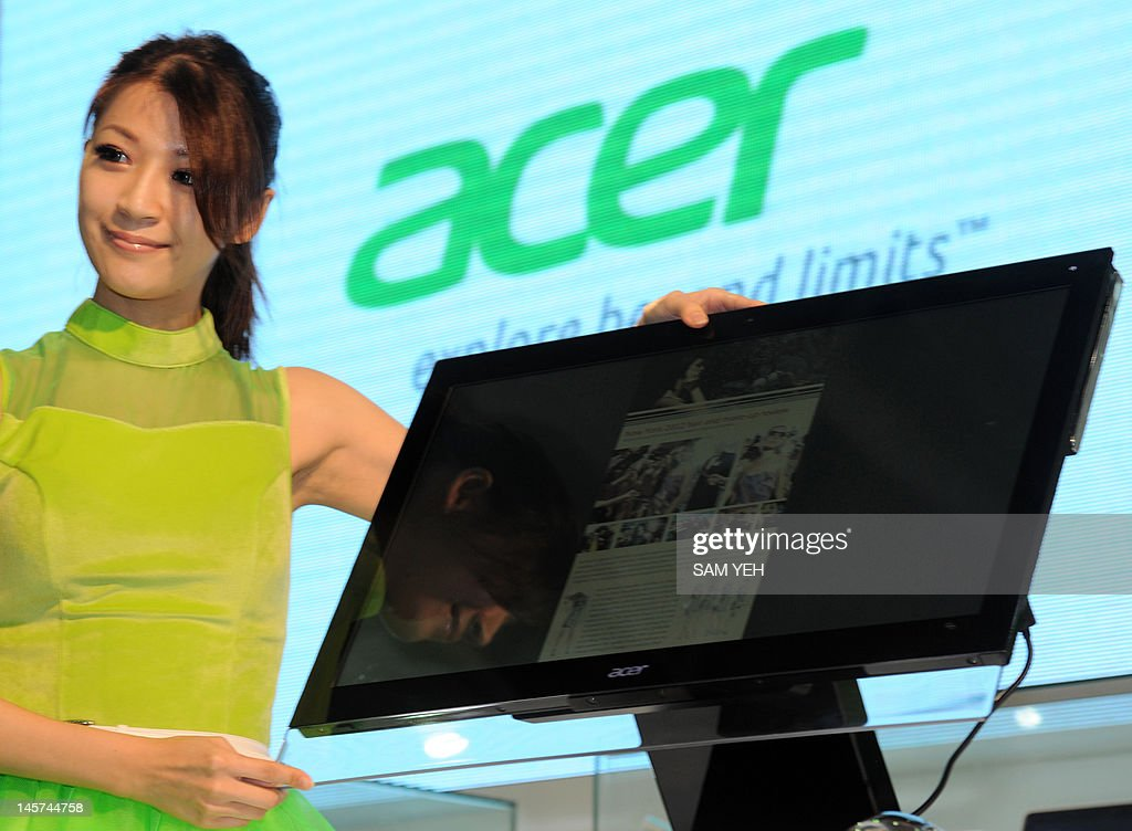 A model shows a monitor in front of Acer's logo during the Computex 2012 in Taipei on June 5, 2012. Taiwan PC makers Acer and Asus took another shot at gaining a foothold in the tablet market, unveiling several new products running on Microsoft's much-anticipated Windows 8 operating system. AFP PHOTO / Sam YEH