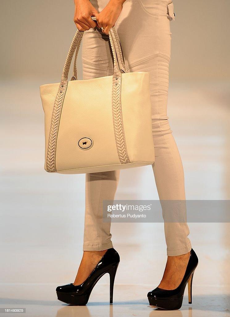 A model shows details of handbag collection as she walks the runway at Braun Buffel show during Ciputra World Fashion Week 2013 on September 21, 2013 in Surabaya, Indonesia.