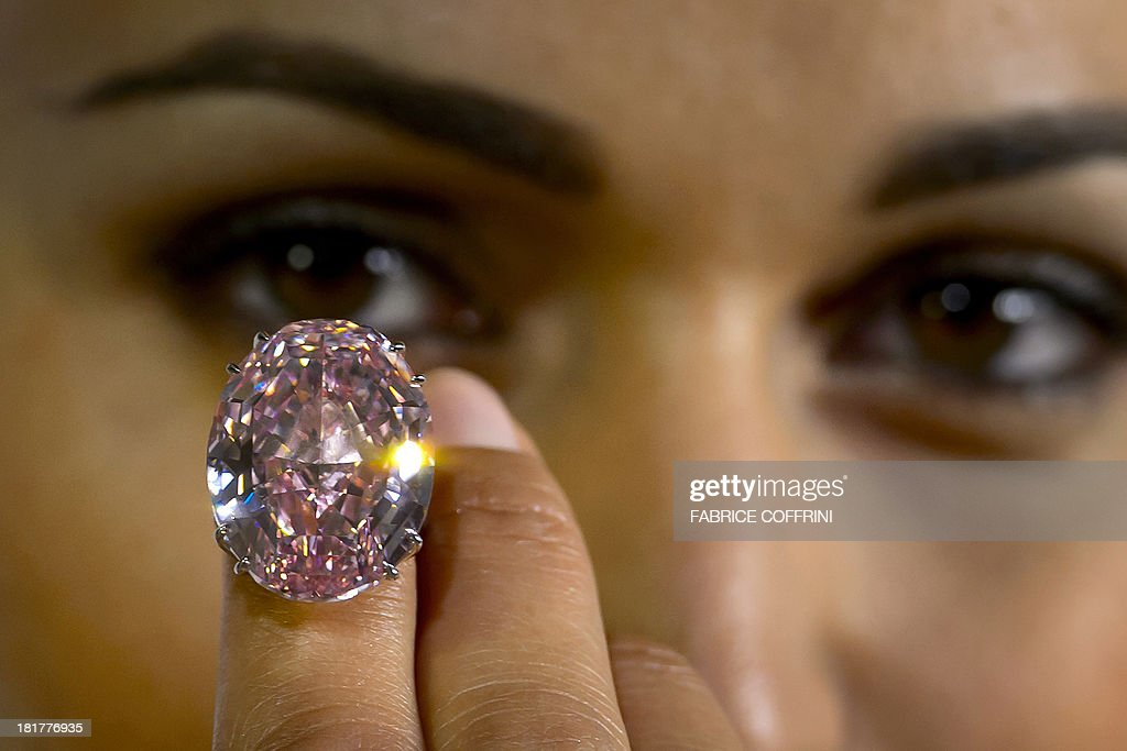 A model shows during a press preview on September 25, 2013 a 59.6-carat pink diamond that will be auctioned by Sotheby's in the Swiss city of Geneva in November at a record asking price of $60 million (49 million euros). 'The Pink Star', an internally flawless oval-cut vivid pink diamond, will become the most valuable diamond ever to be offered at auction, Sotheby's said. AFP PHOTO / FABRICE COFFRINI