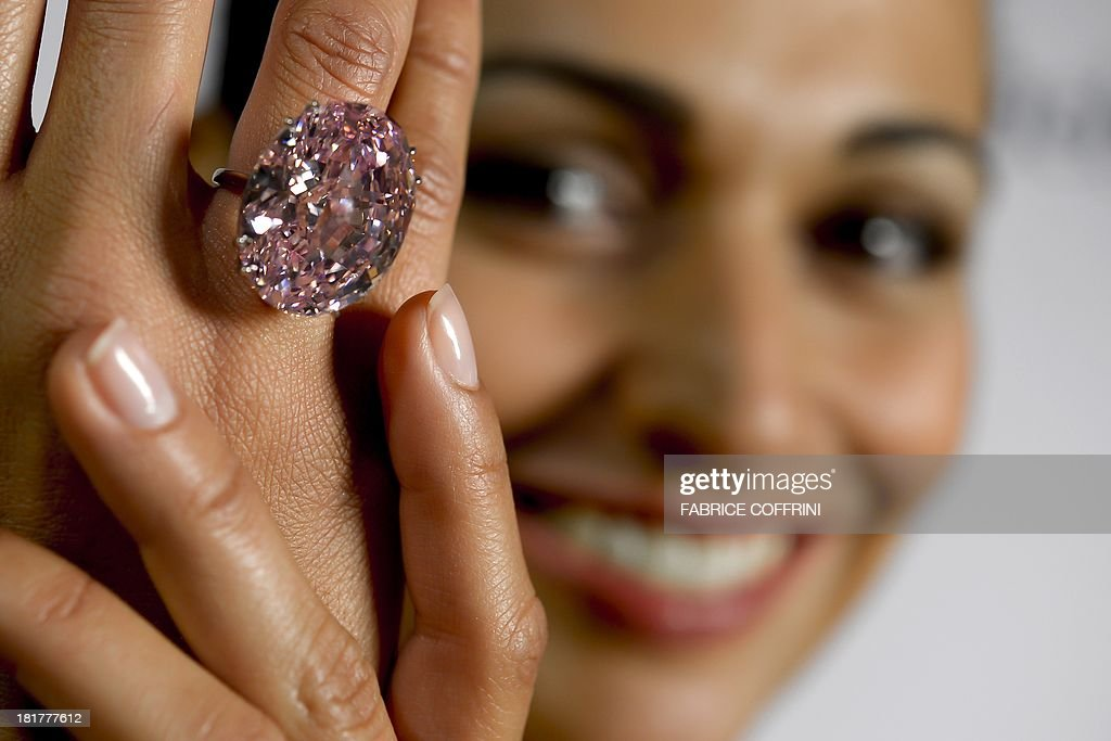 A model shows during a press preview on September 25, 2013 a 59.6-carat pink diamond that will be auctioned by Sotheby's in the Swiss city of Geneva in November at a record asking price of $60 million (49 million euros). 'The Pink Star', an internally flawless oval-cut vivid pink diamond, will become the most valuable diamond ever to be offered at auction, Sotheby's said.