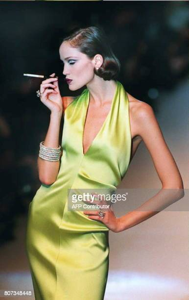 A model shows Gianfranco Ferre's design of a silk cocktail dress with a plunging neckline in a nod to Marlene Dietrich in Christian Dior's...