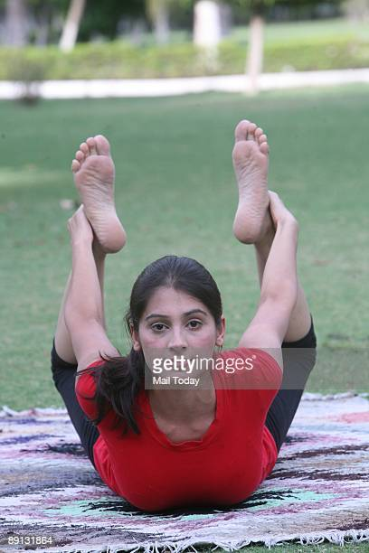 A model shows how to practice Dhanurasana a yoga asan that is good for diabetes and constipation in New Delhi on Friday July 10 2009