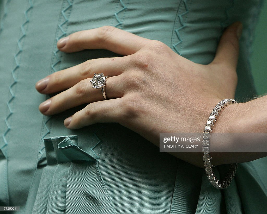 A model shows off a diamond ring and braclet as she stands outside the entrance to the new Wall Street store of Tiffany Co during the opening...