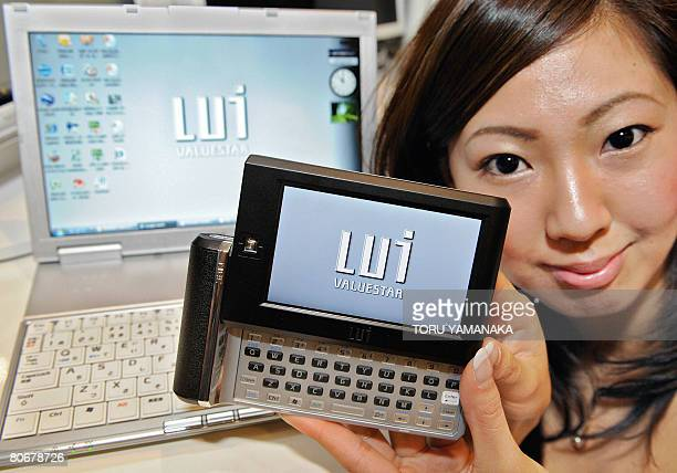 A model shows off a portable remote control unit 'Lui RN' and 'Lui RP' from Japan's electronics giant NEC during a press conference in Tokyo on April...