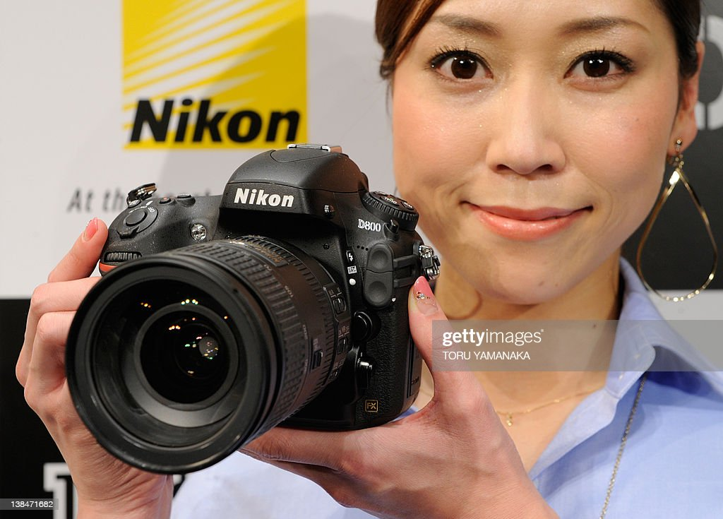 A model shows off the new FX-format digital single lens reflex (SLR) camera 'D800' from Japanese camera maker Nikon, during a press preview in Tokyo on February 7, 2012. Nikon will put the new camera, equipped with the world biggest 36.3 mega-pixel CMOS sensor, a new image processing engine 'EXPEED 3' and 91kilo-pixel RGB sensor, on the market on March 22 at an expected price of 300,000 yen (USD 3,900). AFP PHOTO/Toru YAMANAKA
