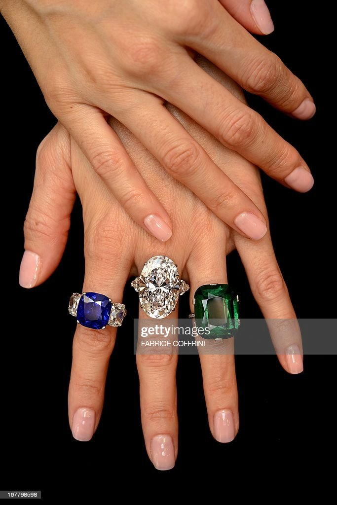 A model shows three rings (L to R) the 'Star of Kashmir', a rarest Kashmir sapphire weighing 19.88 carats, with richly saturated and homogenous cornflower blue colour, estimate SFr.2,400,000-2,900,000 (US$2,500,000-3,000,000), a diamond ring by Graff, set with an oval-shaped, d colour, type IIa 26.24 carats diamond, estimate SFr.2,250,000-3,250,000 (US$2,400,000-3,400,000) and a ring set with a cushion-shaped 23.28 carats Colombian emerald with exceptional size and quality, estimate SFr.1,200,000-1,700,000 (US$1,300,000-1,800,000) during a press preview on April 30, 2013. The rings will be on offer during a sale of magnificent jewels by Christie's auction house on May 15, 2013 in Geneva. AFP PHOTO / FABRICE COFFRINI