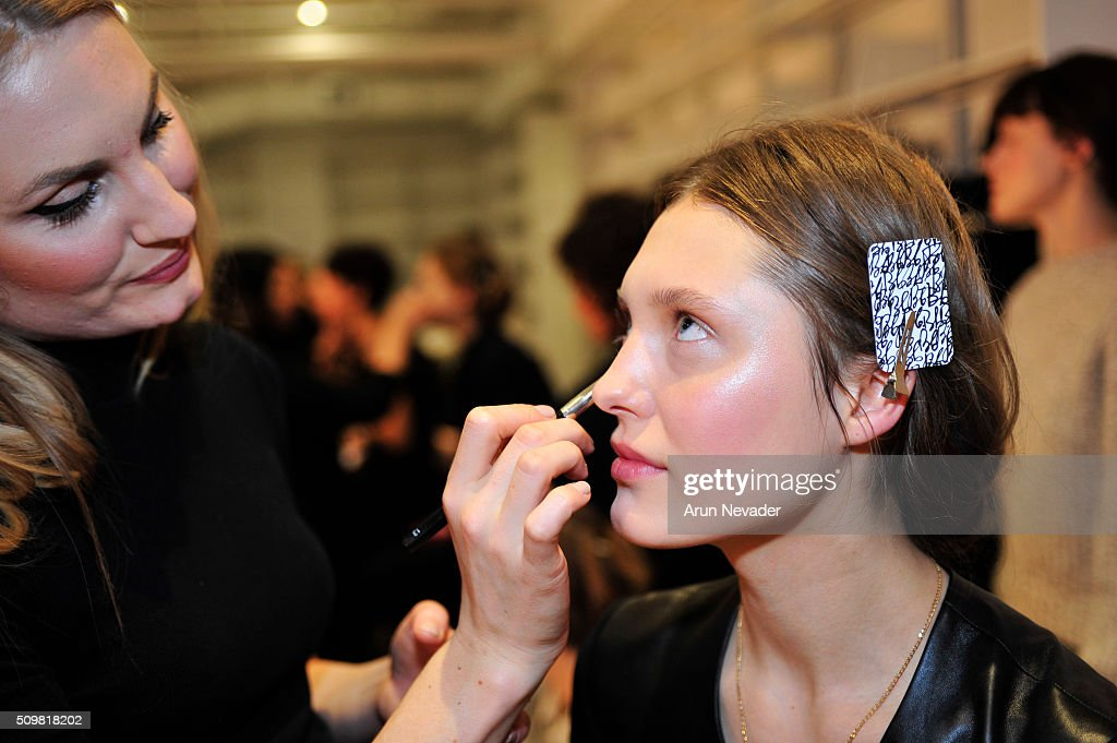 A model sits backstage for hair and makeup for the Tanya Taylor Presentation at Swiss Institute on February 12, 2016 in New York City.