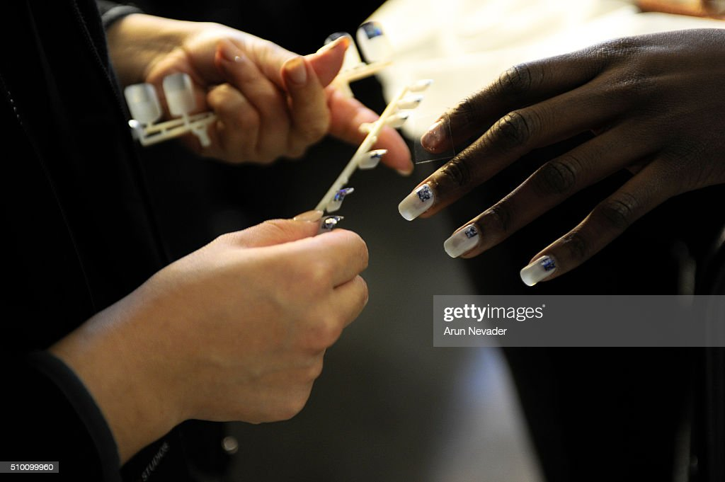 A model sits for fingernail fitting backstage at the Michelle Helene Presentation at Pier 59 on February 13, 2016 in New York City.