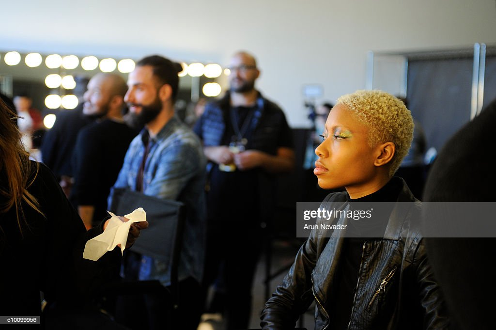 A model sits for makeup backstage at the Michelle Helene Presentation at Pier 59 on February 13, 2016 in New York City.