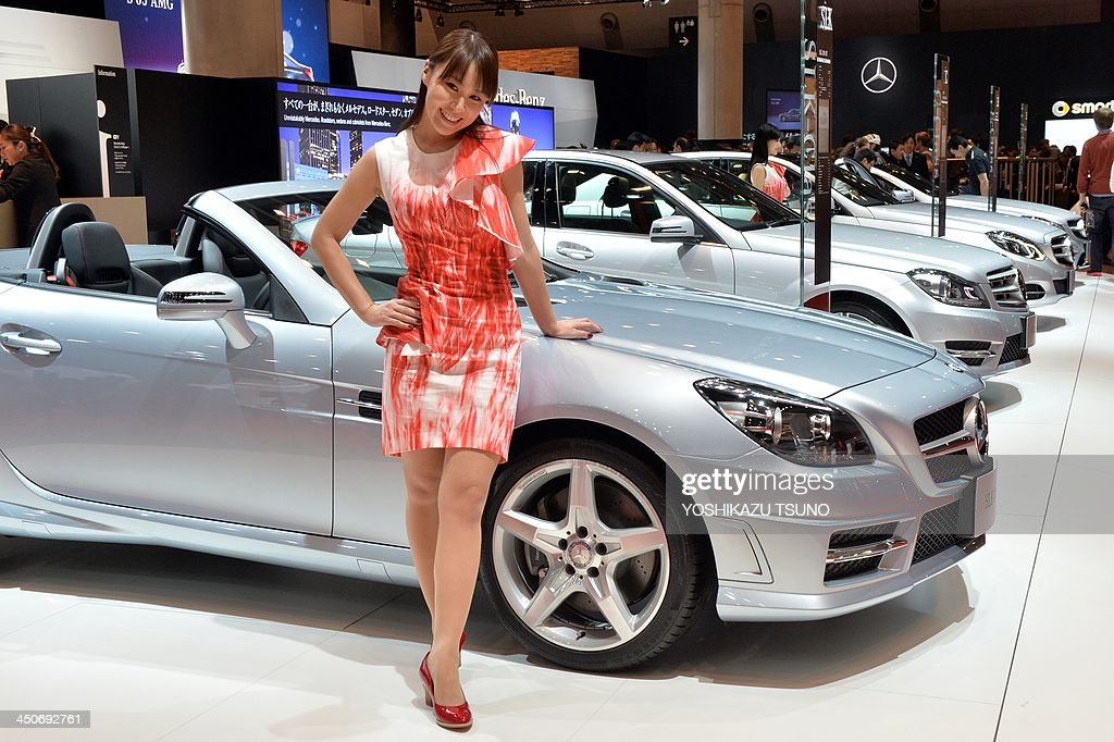 A model smiles next to a line of Mercedes Benz cars up at the press preview of the Tokyo Motor Show in Tokyo on November 20, 2013. The 43rd Tokyo Motor Show runs until December 1 and features 177 exhibitors including parts suppliers from a dozen countries. AFP PHOTO / Yoshikazu TSUNO