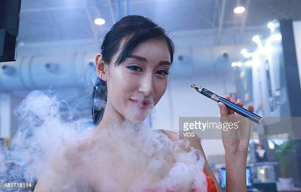 A model smokes an electronic cigarette during the Beijing International Vapor Distribution Alliance Expo at China International Exhibition Center on...