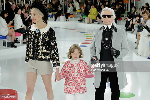 Model Soo Joo Chanel Artistic Director Karl Lagerfeld and his godson Hudson walk in a design by Chanel during the Chanel 2015/16 Cruise Collection on...