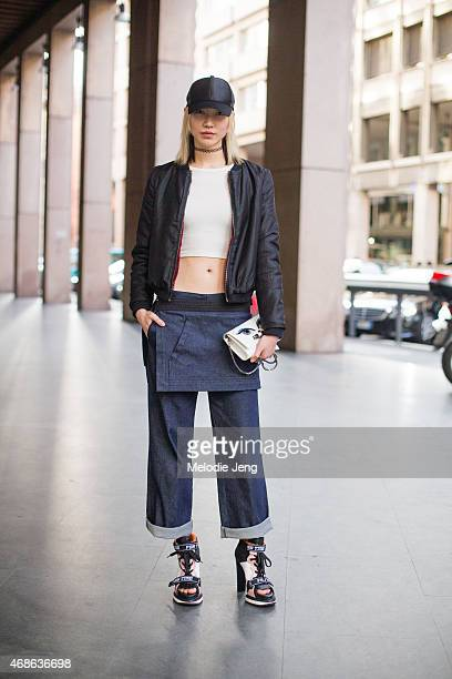 Model Soo Joo Park exits the Fay show in an Acne hat Aritzia top Kara Ross bag and Fay jeans and shoes on Day 1 of Milan Fashion Week FW15 on...