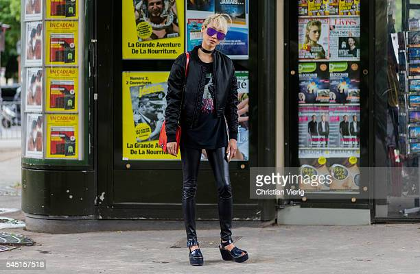 Model Soo Joo Park wearing a Margiela shirt red Dior bag leather pants and black bomber jacket outside Chanel during Paris Fashion Week Haute Couture...