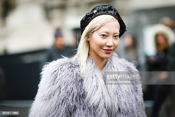 Model Soo Joo Park wears a beret hat and a fur coat outside the Chanel show at the Grand Palais during Paris Fashion Week Haute Couture Spring Summer...