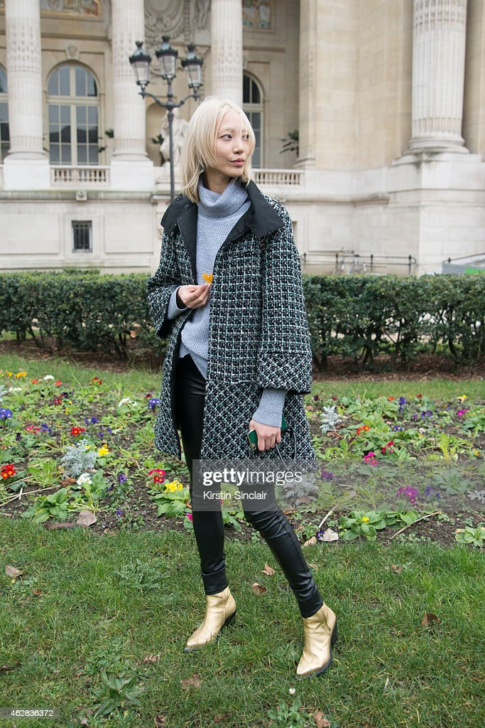 Model Soo Joo Park wears a Chanel coat Barbara Bui boots and Rabeanco handbag on day 3 of Paris Haute Couture Fashion Week Spring/Summer 2015 on...