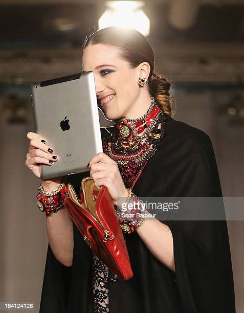 Model Sophie Lowe uses an Ipad as she showcases designs by MIMCO on the runway at the MIMCO show during L'Oreal Melbourne Fashion Festival on March...