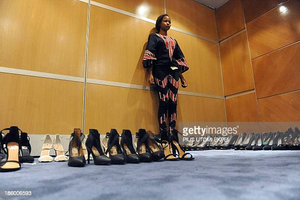 A model standing among pairs of shoes displays a creation by Italian founder of Nigerian based Kinabuti fashion label Caterina Bortolussi during a...