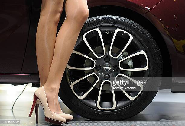 A model stands by an Opel logo on the wheel of the new Opel Adam car at the Paris Auto Show on September 27 2012 in Paris France Opel which has been...