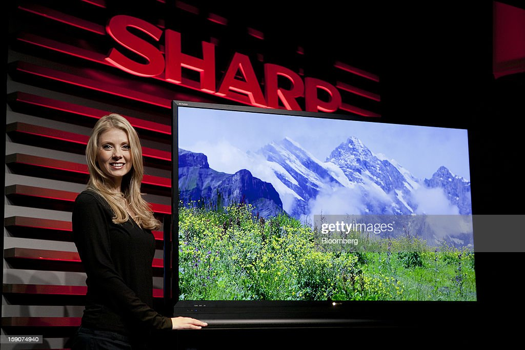 A model stands next to a Sharp Corp. 60-inch ICC Purios television during a news conference prior to the 2013 Consumer Electronics Show in Las Vegas, Nevada, U.S., on Monday, Jan. 7, 2013. The 2013 CES trade show, which runs until Jan. 11, is the world's largest annual innovation event that offers an array of entrepreneur focused exhibits, events and conference sessions for technology entrepreneurs. Photographer: Andrew Harrer/Bloomberg via Getty Images