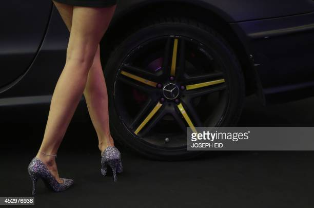 A model stands next to a sports car during the Lebanon Motorsport and Tuning Show 2014 in Jounieh north of Beirut on July 31 2014 The show exhibited...