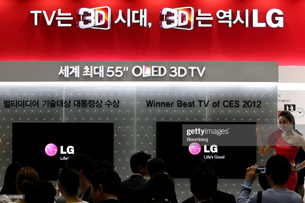 A model stands next to LG Electronics Inc.'s 55 inch organic light emitting diode (OLED) 3-D televisions at the World IT Show 2012 at the World IT Show 2012 in Seoul, South Korea, on Tuesday, May 15, 2012. The show will be held through May 18. Photographer: SeongJoon Cho/Bloomberg via Getty Images