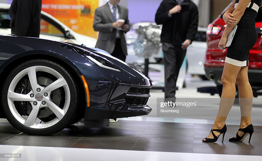 A model stands next to the 2014 Chevrolet Corvette on display at the company's booth during the 2013 New York International Auto Show in New York, U.S., on Thursday, March 28, 2013. The 113th New York International Auto Show, which runs from March 29 to April 7, features 1,000 vehicles as well the latest in tech, safety and innovation. Photographer: Jin Lee/Bloomberg via Getty Images