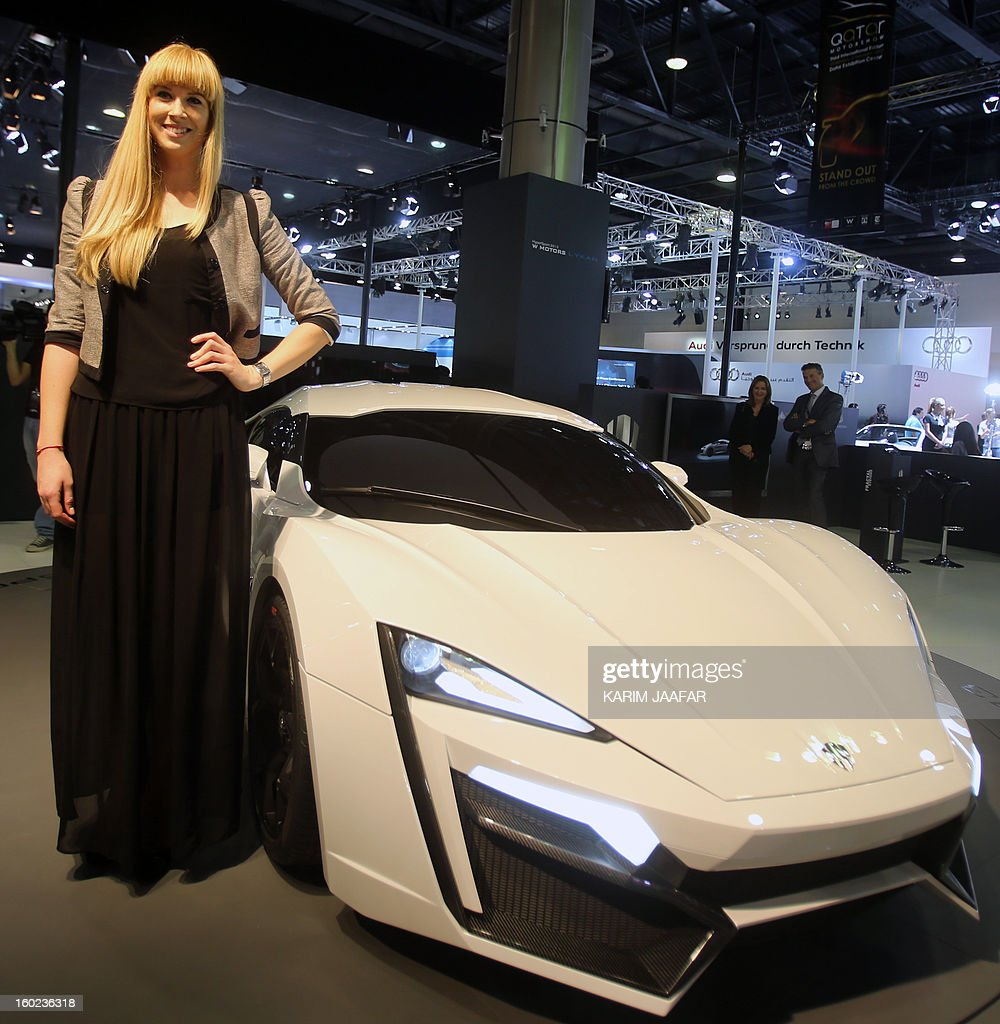 A Model stands next to the first Arabian supercar, LykanHypersport during the third International Qatar Auto Show on January 28, 2013 in Doha. Created by Beirut-based W Motors the LykanHypersport is labeled as the most exclusive, luxurious and technologically advanced Hypercar in the world that boasts never seen before cutting-edge technologies inside and out. AFP PHOTO / AL-WATAN DOHA / KARIM JAAFAR == QATAR OUT ==